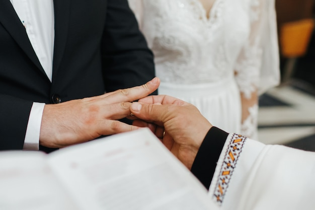 Hochzeitszeremonie. priester legt ehering auf die hand des bräutigams Kostenlose Fotos