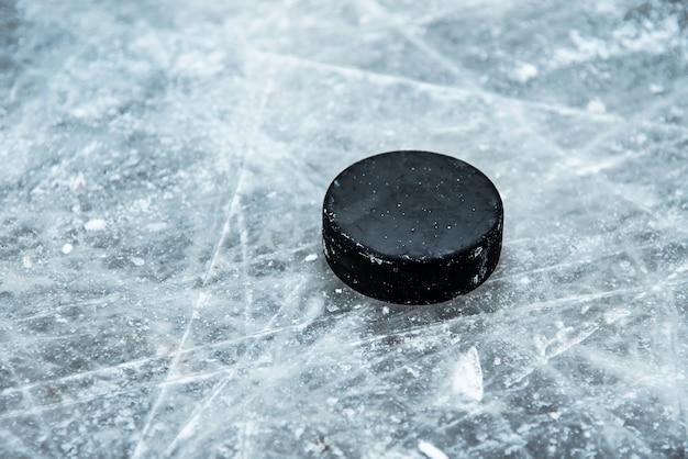 Hockey-puck liegt auf der schneenahaufnahme Premium Fotos