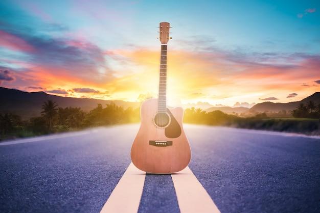 Hölzerne akustikgitarre, die auf straße mit sonnenaufganghintergrund, reise des musikerkonzeptes liegt Premium Fotos