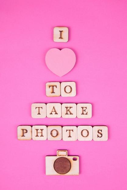 Hölzerne buchstaben, aufschrift auf einem hellen rosa hintergrund Premium Fotos
