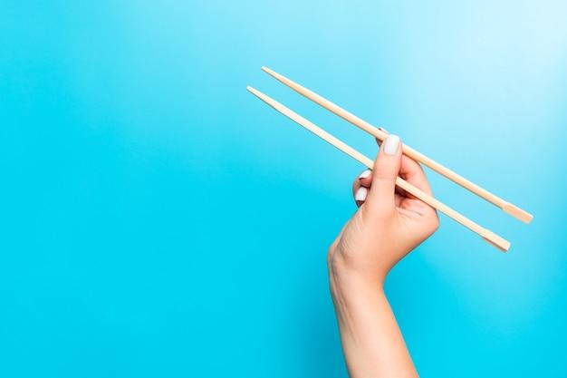 Hölzerne essstäbchen gehalten mit den weiblichen händen auf blau. essfertige s mit leeren raum Premium Fotos