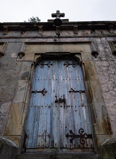 Hölzerne kirchentür des blauen schmutzes in der backsteinmauer. Premium Fotos