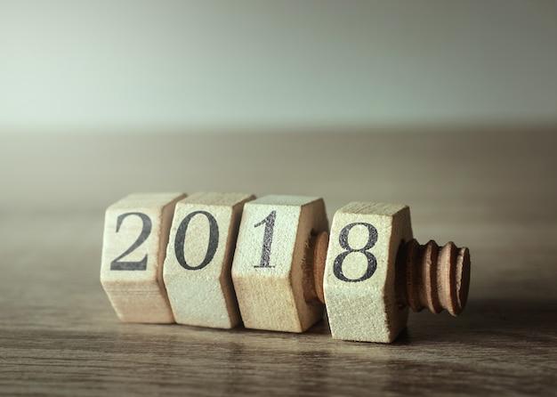 Hölzerne nuss und bolzen auf hölzerner tabelle mit neujahrszahl 2018. Premium Fotos