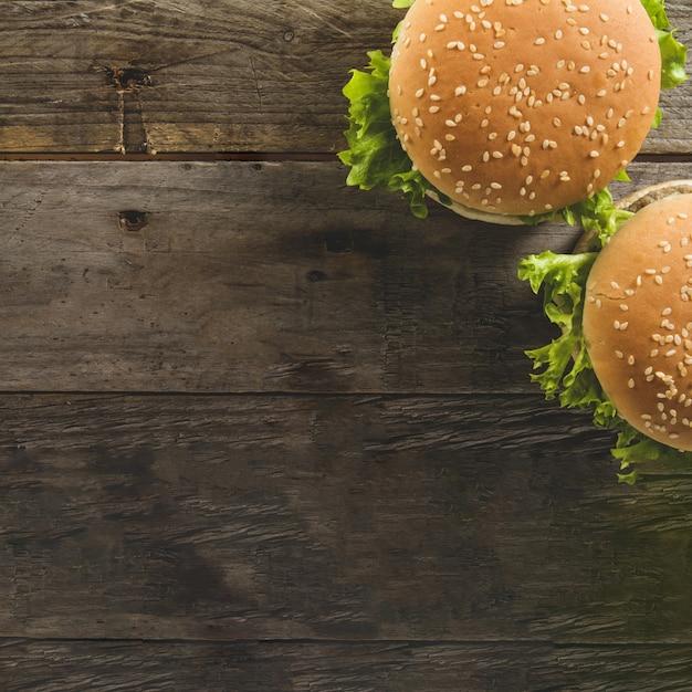 Hölzerne oberfläche mit zwei burger und leerzeichen Kostenlose Fotos