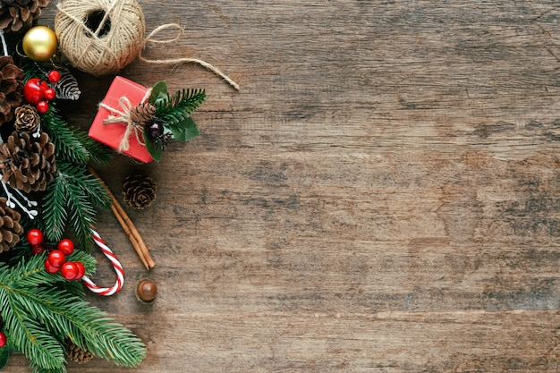 Hölzerne planke mit kiefernblättern, kiefernkegeln, stechpalmenbällen, geschenkbox und zuckerstange im weihnachtskonzept. Premium Fotos