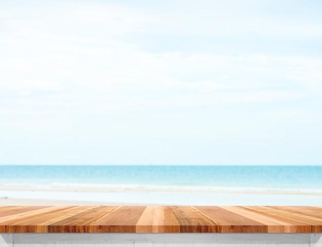 Hölzerne plankentischplatte mit unscharfem meer und blauem himmel am hintergrund Premium Fotos