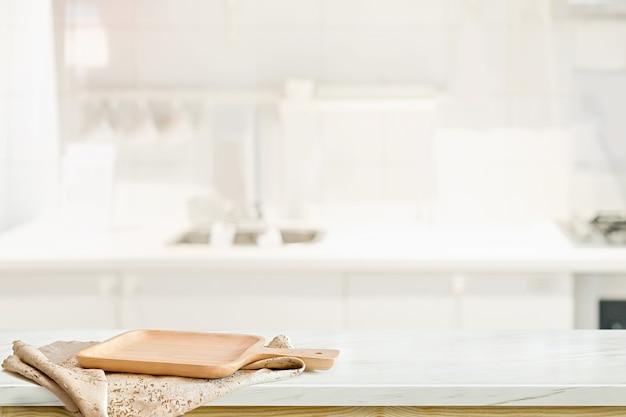 Hölzerne platte auf weißer tabelle im küchenraumhintergrund Premium Fotos