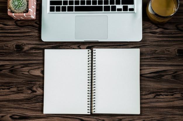 Hölzerne schreibtischtabelle browns mit einem buch, einem stift, einem kaktus und einem telefon für das arbeiten Premium Fotos