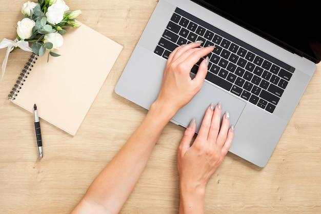 Hölzerne schreibtischtabelle mit laptop-computer, weibliche hände, die auf tastatur, papiernotizbuch, blumenstrauß von blumen schreiben. Premium Fotos