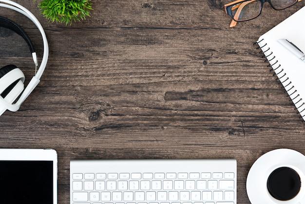 Hölzerne schreibtischtabelle und -ausrüstung browns für das bearbeiten und hörende musik mit weißem kopfhörer im draufsicht- und kopienraum. Premium Fotos