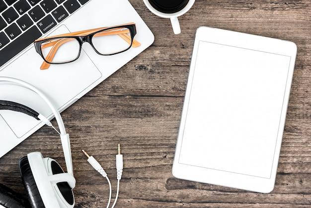Hölzerne schreibtischtabelle und -ausrüstung browns für das bearbeiten und hörende musik mit weißer tablette des kopfhörers und des weißen leeren bildschirms im draufsicht- und kopienraum. Premium Fotos