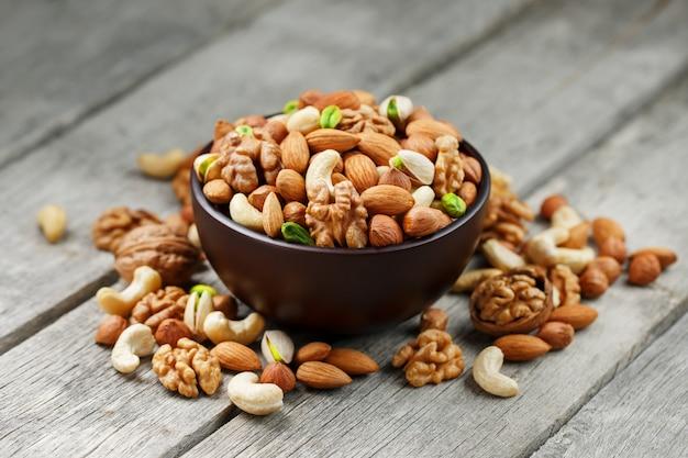 Hölzerne schüssel mit mischnüssen auf einem hölzernen grau. walnuss, pistazien, mandeln, haselnüsse und cashewnüsse, walnuss. Premium Fotos