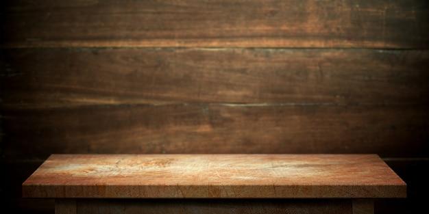 Hölzerne tabelle auf dunkelbrauner wand unscharfer hintergrund. Premium Fotos