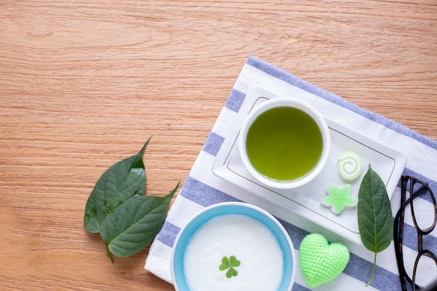 Hölzerne tabelle der küche mit schale matcha grünem tee und organischem joghurt. Premium Fotos
