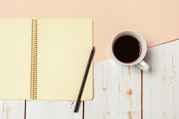 Hölzerne tabelle des büros mit leerem notizblock, bleistift. Premium Fotos
