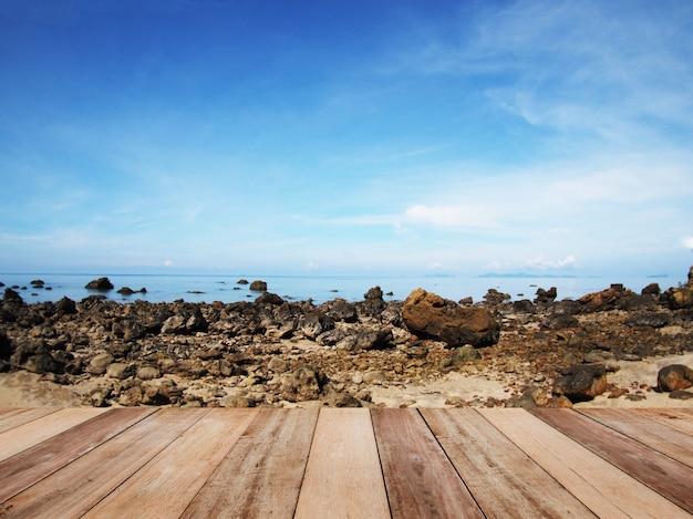 Hölzerne tabelle für anzeigenprodukt mit ansichten zum strand und zum blauen himmel Premium Fotos