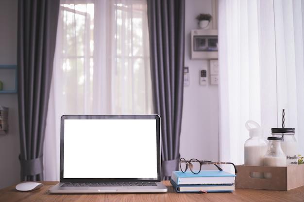 Hölzerne tabelle mit leerem bildschirm auf laptop, notizbuchpapier und milch auf kastenkarton im wohnzimmer. Premium Fotos