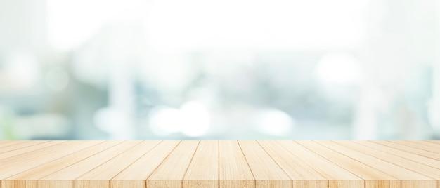 Hölzerne tischplatte an mit unschärfeglasfensterwandhintergrund. Premium Fotos