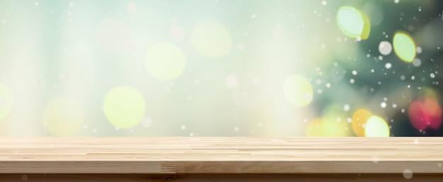 Hölzerne tischplatte auf bokeh-hintergrund von verziertem weihnachtsbaum, panoramische fahne Premium Fotos