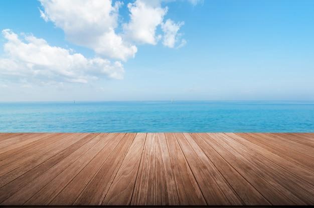 Hölzerne tischplatte auf unscharfem blauem meer und himmel Premium Fotos