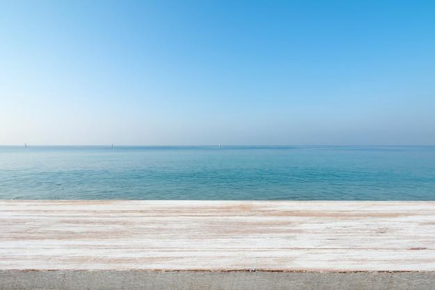 Hölzerne tischplatte auf unscharfem blauem meer und weißem sandstrandhintergrund Premium Fotos