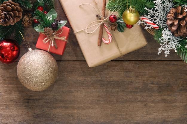 Hölzerne tischplatte mit kiefernblättern und zapfen, stechpalmenkugeln, goldener kugel des funkelns und geschenkbox Premium Fotos