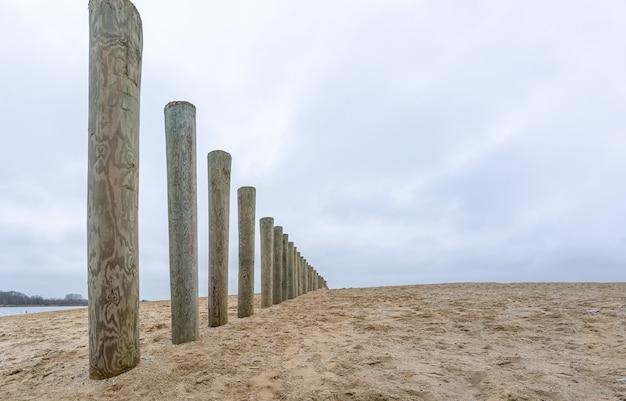 Hölzerne wellenbrecherstangen an einem strand unter einem bewölkten himmel während des tages Kostenlose Fotos