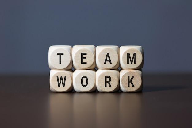 Hölzerne würfelelemente mit buchstaben auf holztisch, der teamwork darstellt. unternehmenskonzept. Premium Fotos