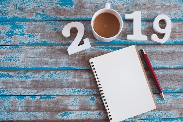 Hölzerne zahl und heißer kaffee mit text 2019 und notizbuch auf rustikalem blauem holztisch Premium Fotos