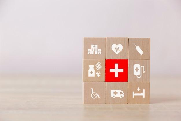 Hölzerner block der krankenversicherung, der mit dem ikonengesundheitswesen medizinisch stapelt. Premium Fotos