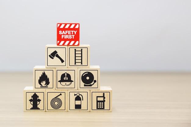 Hölzerner block, der mit feuer- und sicherheitsikonen stapelt. Premium Fotos