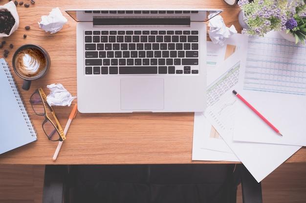 Hölzerner bürotisch mit laptop und schreibarbeit, lattekaffeetasse, zerknittertes papier. Premium Fotos