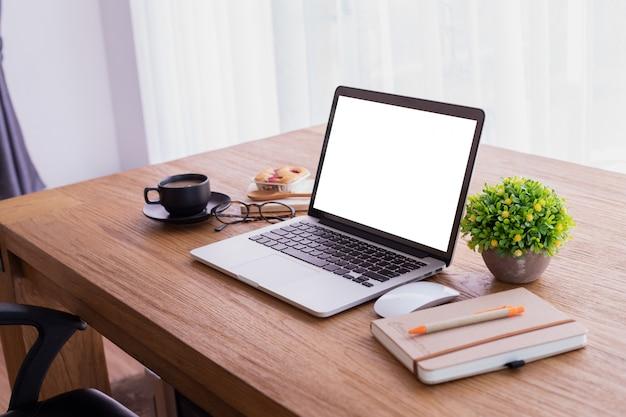 Hölzerner bürotisch mit leerem bildschirm auf laptop zu hause, kopienraum, spitzentabelle. Premium Fotos