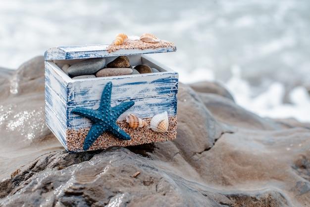 Hölzerner dekorativer kasten mit muscheln und blauer stern auf der seeküste. Premium Fotos