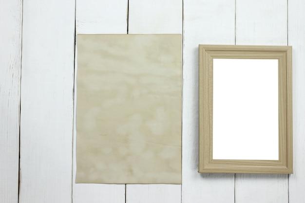 Hölzerner fotorahmen und altes leeres weinlesepapier auf weißem bretterboden. Premium Fotos