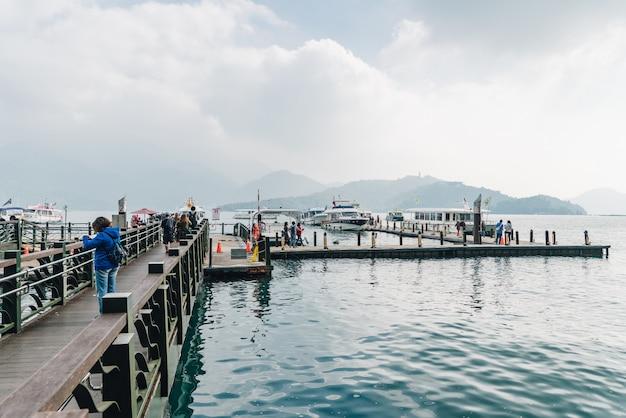 Hölzerner gehweg, der zum boot in sun moon lake mit berg und wolke führt Premium Fotos