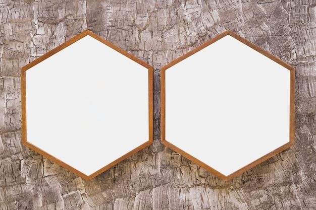 Hölzerner hexagonrahmen mit zwei weiß auf tapete Kostenlose Fotos