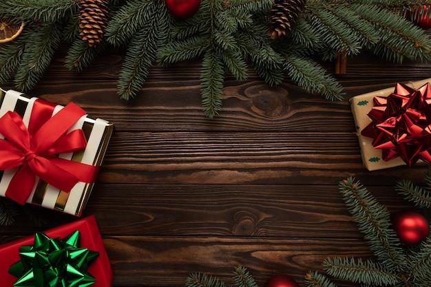 Hölzerner hintergrund verziert mit weihnachtsdekorationen und geschenken. Premium Fotos
