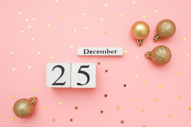 Hölzerner kalender am 25. dezember, goldene weihnachtsbälle und sternkonfettis auf rosa wand. frohe weihnachten-konzept. Premium Fotos