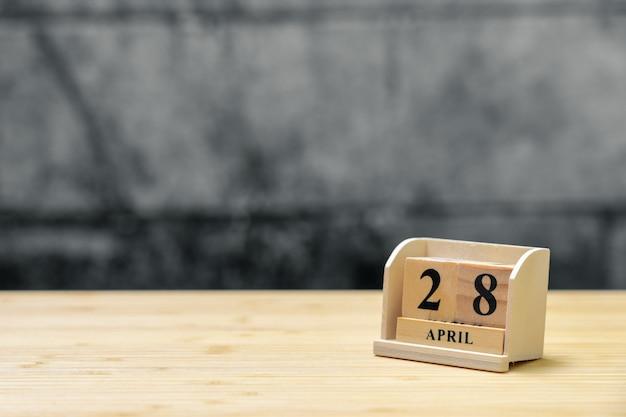 Hölzerner kalender am 28. april auf hölzernem abstraktem hintergrund der weinlese. Premium Fotos