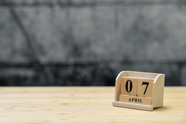 Hölzerner kalender am 7. april auf hölzernem abstraktem hintergrund der weinlese. Premium Fotos