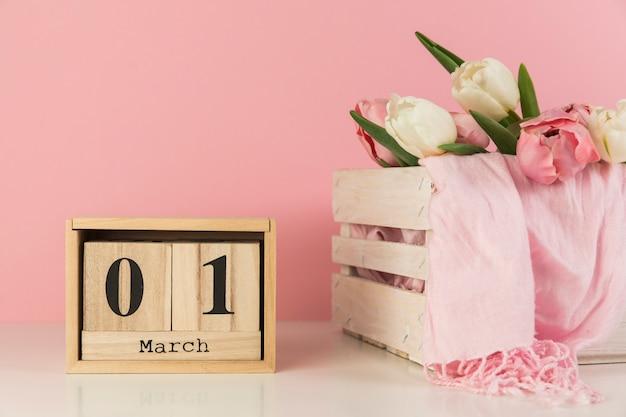 Hölzerner kalender, der 1. märz nahe der kiste mit tulpen und schal gegen rosa hintergrund zeigt Kostenlose Fotos