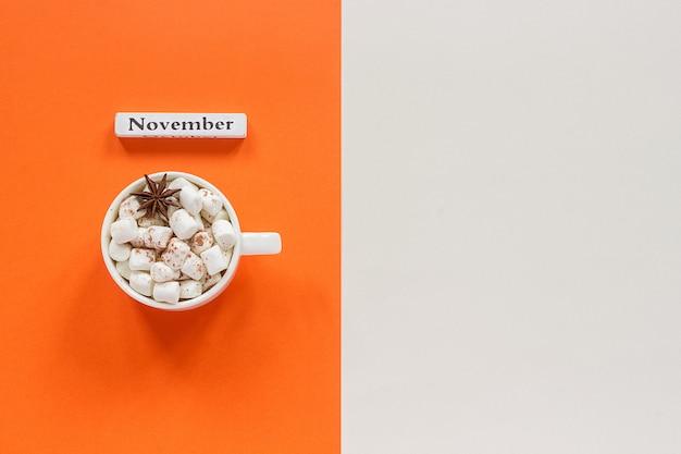 Hölzerner kalendermonat november und schale kakao mit eibischen auf orange beige hintergrund. Premium Fotos