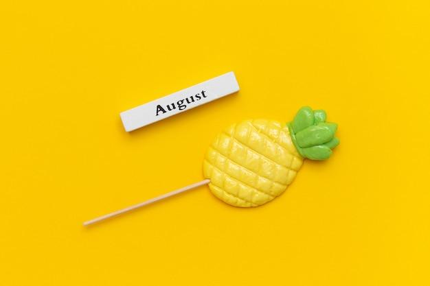 Hölzerner kalendersommermonat august und ananaslutscher auf stock auf gelbem hintergrund Premium Fotos