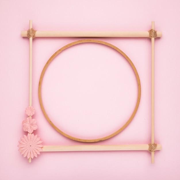 Hölzerner kreis innerhalb des quadratischen rahmens auf rosa hintergrund Kostenlose Fotos