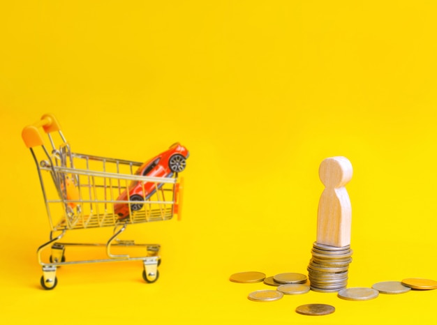 Hölzerner mannstand auf münzen auf dem hintergrund eines autos und eines korbes von einem supermarkt. Premium Fotos