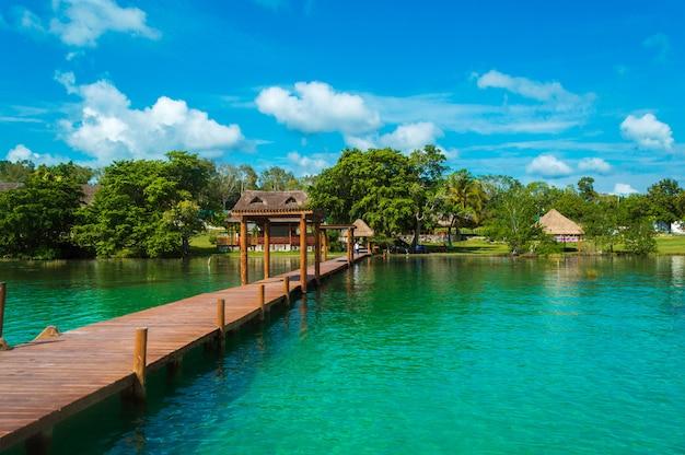 Hölzerner pier in der lagune der sieben farben mit schöner landschaft. das kristallklare wasser der bacalar lagune, quintana roo, mexiko. Premium Fotos