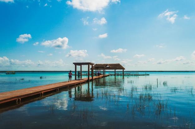 Hölzerner pier in der lagune der sieben farben mit schöner landschaft. leute, die das haarscharfe wasser der bacalar-lagune, quintana roo, mexiko genießen Premium Fotos