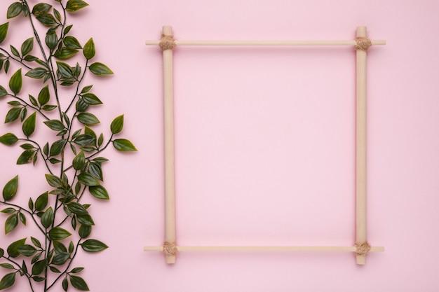 Hölzerner quadratischer rahmen mit künstlichem grün verlässt auf rosa hintergrund Kostenlose Fotos