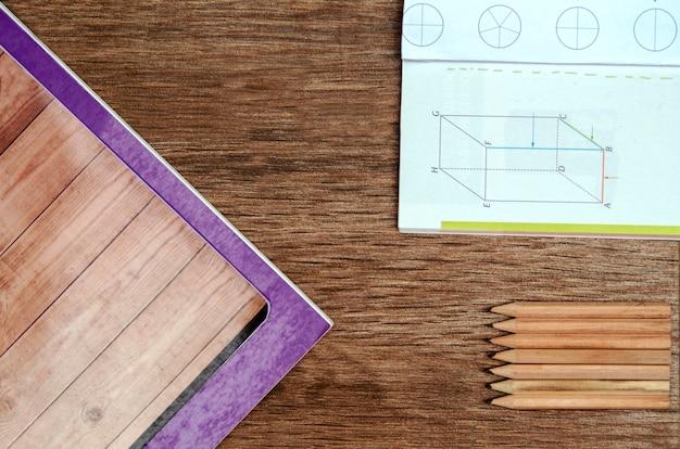 Hölzerner schreibtisch der schule mit papierbuch, bleistiften und mathematikbuch schulbank Premium Fotos
